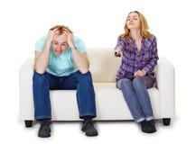 Marido nervioso y esposa que se sientan en el sofá Imagen de archivo