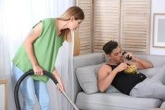 Marido perezoso que miente en el sofá y su limpieza de la esposa fotografía de archivo libre de regalías
