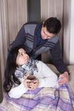 Marido que ajuda sua esposa doente com gripe Imagem de Stock