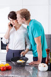 Marido que besa a su esposa durante la preparación del desayuno Imagen de archivo
