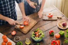 Marido que cozinha a salada do jantar quando sua esposa beber o vinho Fotografia de Stock Royalty Free