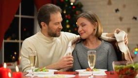 Marido que cubre a la esposa joven con la tela escocesa acogedora, celebrando víspera de Navidad, relaciones almacen de metraje de vídeo