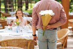 Marido que cuida que presenta las flores agradables a la esposa Imagenes de archivo