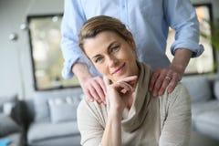Marido que dá a massagem de relaxamento do ombro a sua esposa Imagem de Stock Royalty Free