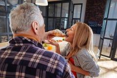 Marido que da el cruasán delicioso a la esposa por la mañana imagenes de archivo