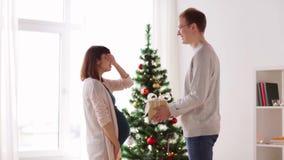 Marido que da el regalo de Navidad a la esposa embarazada metrajes
