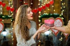 Marido que da a la esposa presente en el día del ` s de la tarjeta del día de San Valentín Imágenes de archivo libres de regalías