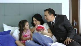 Marido que da un regalo a su esposa con la hija en el dormitorio almacen de metraje de vídeo