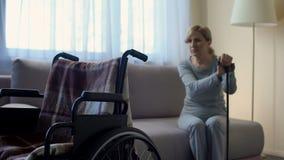 Marido que espera jubilado triste de la señora para en el hospital, mirando la silla de ruedas, rehabilitación almacen de metraje de vídeo