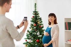 Marido que fotografa o pífano grávido no Natal Fotografia de Stock Royalty Free