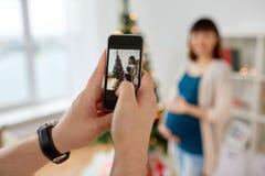 Marido que fotografa o pífano grávido no Natal Imagem de Stock
