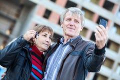 Marido que hace el selfie por el teléfono cuando esposa que lleva a cabo llaves de la casa disponibles Imágenes de archivo libres de regalías