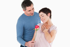 Marido que ofrece una rosa a su esposa sonriente Imagen de archivo