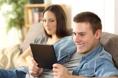 Marido que olha o índice em linha e que ignora sua esposa fotografia de stock royalty free