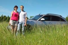 Marido, soporte de la esposa cerca del coche Imágenes de archivo libres de regalías