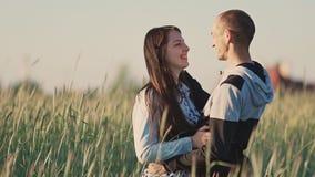 Marido y esposa en un campo del trigo entre los rayos en la puesta del sol Se abrazan Beso feliz junto almacen de metraje de vídeo