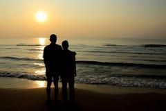 Marido y esposa que abrazan en el mar, silueta Imagenes de archivo