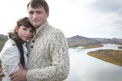 Marido y esposa que abrazan en una montaña Fotos de archivo