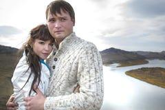 Marido y esposa que abrazan en una montaña Imágenes de archivo libres de regalías