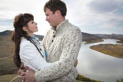 Marido y esposa que abrazan en una montaña Foto de archivo libre de regalías