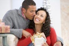 Marido y esposa que intercambian los regalos de la Navidad Imagen de archivo libre de regalías