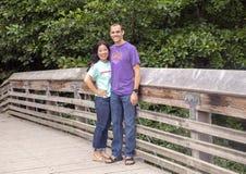 Marido y esposa que presentan en un puente de madera en Washington Park Arboretum, Seattle, Washington foto de archivo libre de regalías