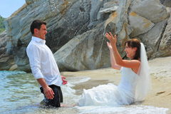 Mariée éclaboussant le marié de l'eau de mer Photos stock