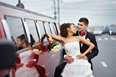 Mariée et marié heureux près de limousine de mariage Photographie stock libre de droits