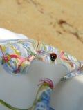 Marienkäfer auf weißem Gewebe mit einer Verzierung Stockfoto