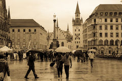 Marienplatz and the old City hall. Munich. Germany. People walking in the rain in Marienplatz, the old City hall (altes rathaus) in the background. Munich royalty free stock photo