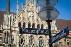 Marienplatz street sign over Munich town hall. Marienplatz - street and square name in the very center of Munich old town. Blurred Rathaus on the background royalty free stock photography