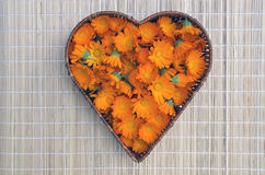 Marigold calendula medical flowers in heart form wicker basket Stock Photos