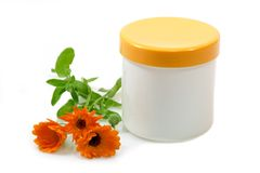 Marigold Hand-Care. Cream pot with marigold on white background Royalty Free Stock Image