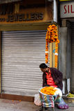 Marigold seller in Delhi, India. Street scene in Delhi, India with overhead electrical wires royalty free stock photography