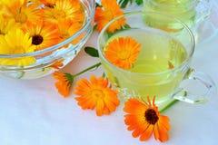 Marigold tea and flowers. Calendula tea in glass cups and pot marigold flowers stock photo