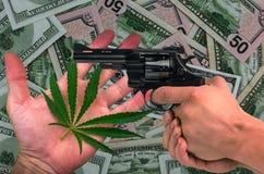 Marihuana, Gewehr in seinen Händen auf dem Dollarhintergrund Lizenzfreies Stockfoto