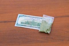 Marihuana im Paket und 100 Dollarschein auf dem Holztisch Lizenzfreie Stockbilder
