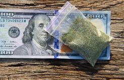 Marihuana im Paket und 100 Dollarschein auf Holztisch Lizenzfreies Stockfoto