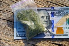 Marihuana im Paket und 100 Dollarschein auf Holztisch Stockbild
