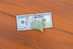 Marihuana im Paket und 100 Dollarschein auf Holztisch Lizenzfreie Stockbilder