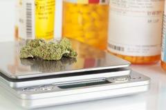 Marihuana-Knospen auf Skala-Verordnungs-Flaschen Stockfotos