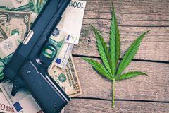 Marihuana leaf with banknotes and weapon. On the table Stock Photos