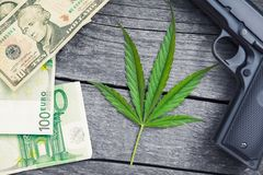 Marihuana leaf.Gun and money around leaf. Marihuana leaf.Gun and money around leaf on wooden background Stock Photo
