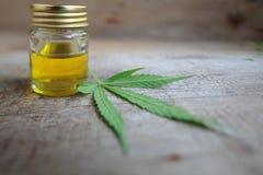 Marihuana leaf i butelka konopianego oleju drewniany stół obrazy royalty free