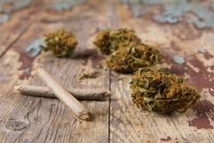 Marihuana pączkuje i złącza na nieociosanym drewnianym stole Zdjęcia Royalty Free