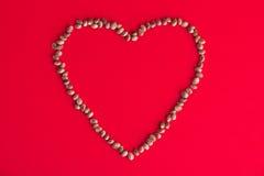 Marihuana & x28; hemp& x29; ziarna tworzy serce nad czerwonym tłem - medi Obraz Stock
