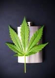 Marihuanablatt auf einer Hüftenflasche stockbilder