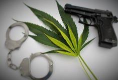 Marihuanahanfblätter und handciffs und Gewehr Stockbild