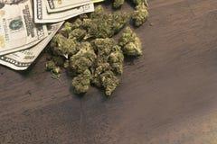 Marihuanaknoppen op lijst met geldachtergrond Stock Afbeeldingen