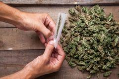 Marihuanaknospen und hande meking Gelenk Lizenzfreie Stockfotografie